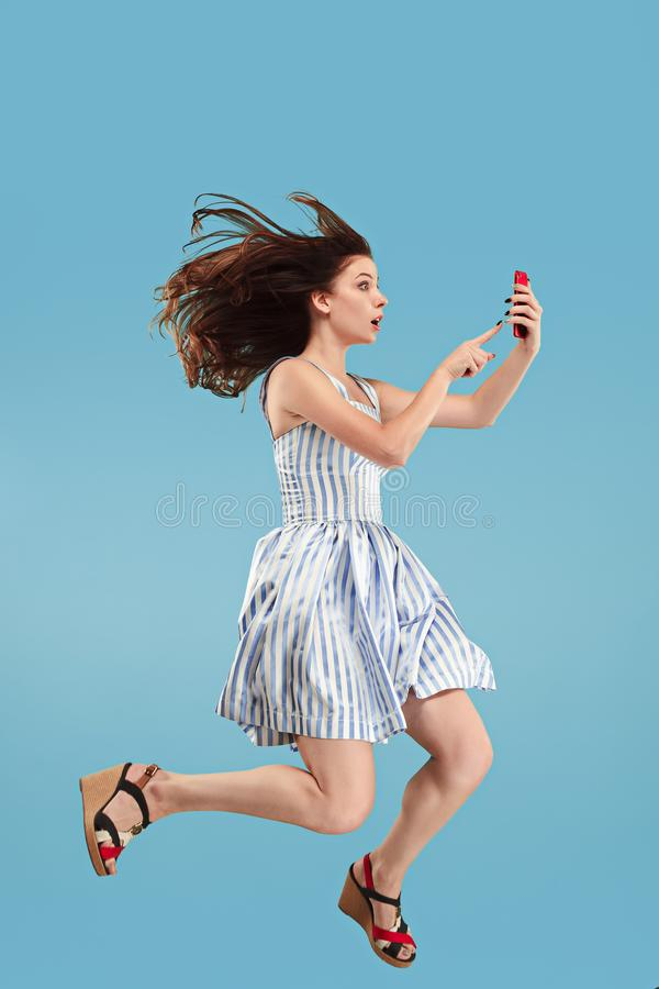 Full length of pretty young woman with mobile phone while jumping. Always on mobile. Full length of pretty young woman taking phone while jumping against blue royalty free stock photos
