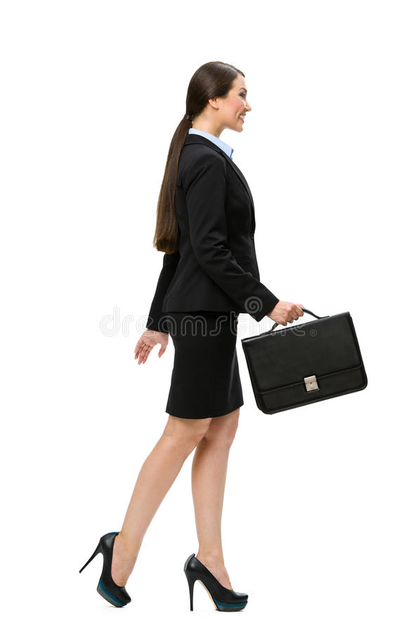 Full-length profile of businesswoman with case. Full-length profile of walking businesswoman with case, isolated on white. Concept of leadership and success stock image