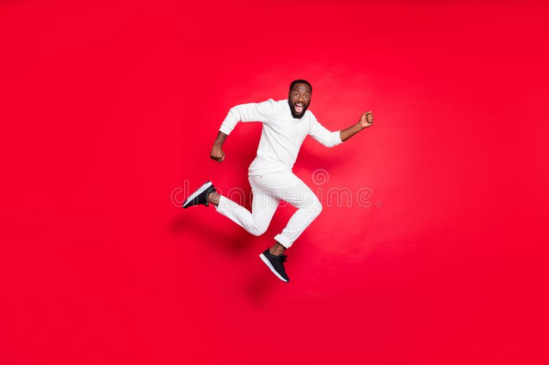 Full length profile photo of excited dark skin guy jumping high running x-mas shopping need buy many presents wear white. Full length profile photo of excited stock images