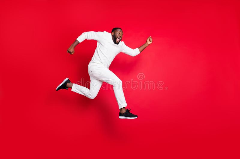 Full length profile photo of excited dark skin man jump high running x-mas shopping need buy many presents wear white. Full length profile photo of excited dark stock image