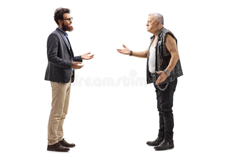 Bearded man having a conversation with an angry male punker in a leather vest royalty free stock image