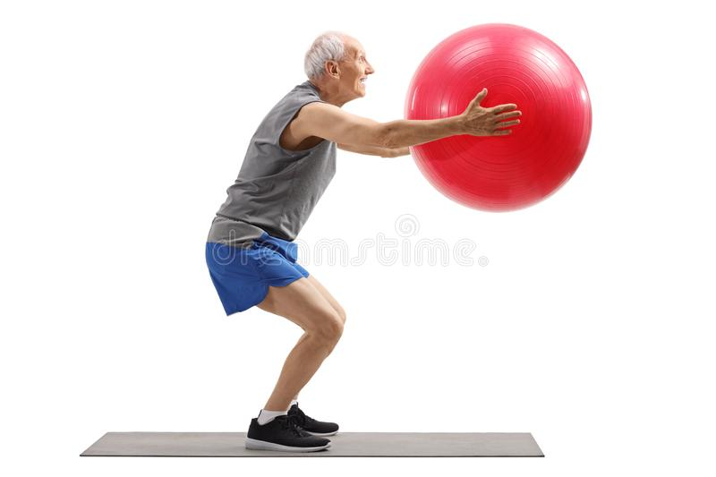 Elderly man exercising with a fitness ball on a mat. Full length profile shot of an elderly man exercising with a fitness ball on a mat isolated on white stock photos