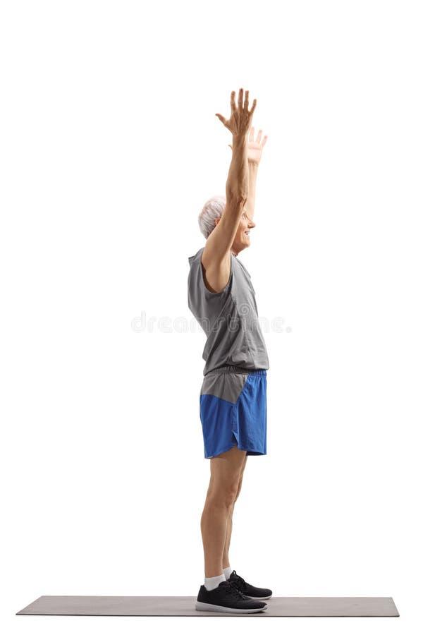Elderly man exercising on a mat. Full length profile shot of an elderly man exercising on a mat isolated on white background royalty free stock photography