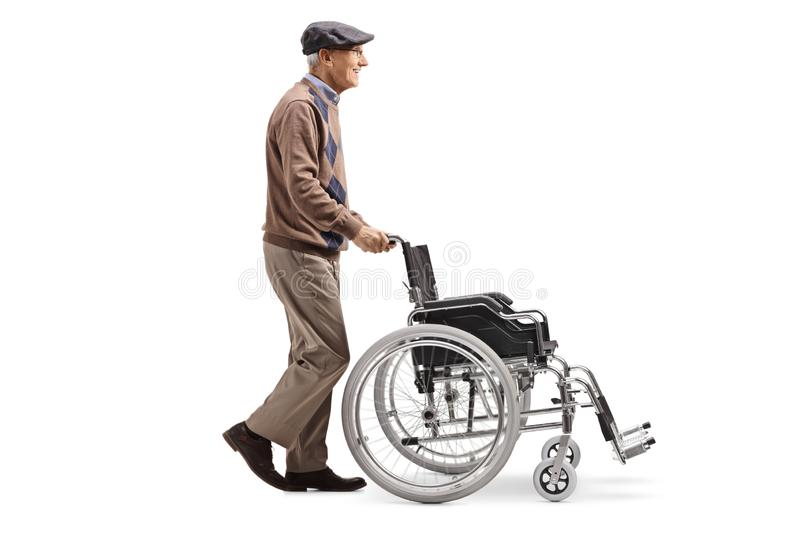 Elderly man pushing an empty wheelchair. Full length profile shot of an elderly man pushing an empty wheelchair isolated on white background stock photo