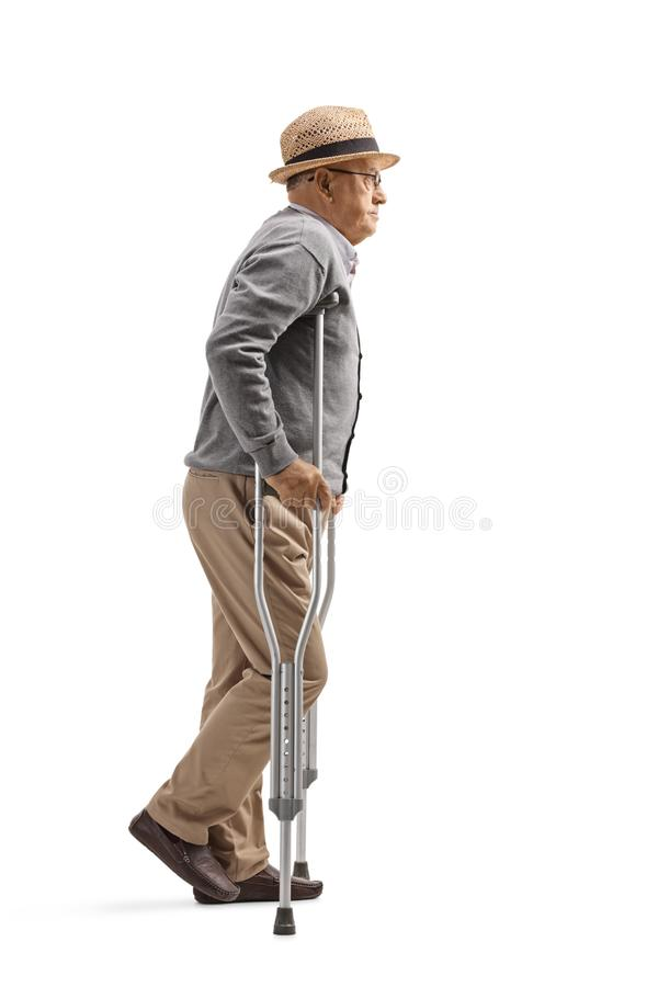 Elderly man walking with crutches. Full length profile shot of an elderly man walking with crutches isolated on white background royalty free stock photo