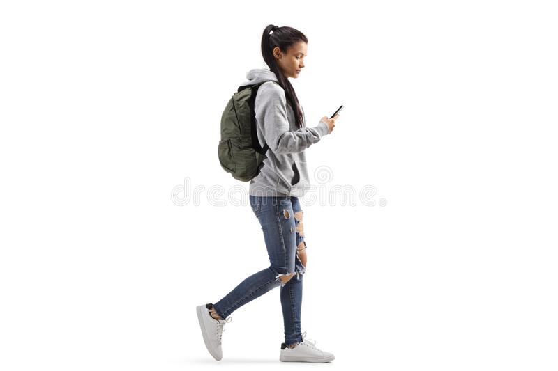 Female student with a backpack walking and looking into a mobile phone stock images
