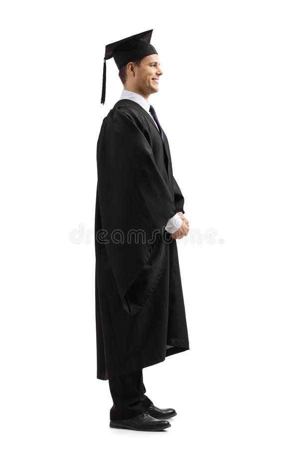 Happy young man in graduation gown. Full length profile shot of a happy young man in graduation gown isolated on white background royalty free stock photo