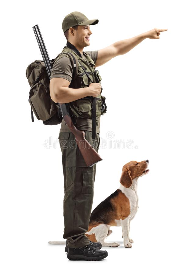 Hunter with a dog pointing. Full length profile shot of a hunter with a dog pointing isolated on white background stock image