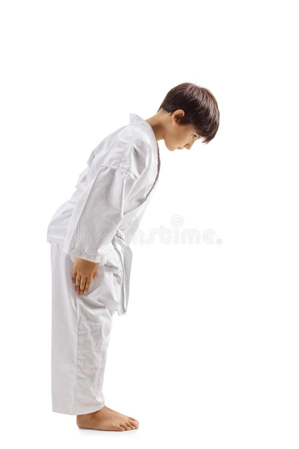Karate kid bowing. Full length profile shot of a karate kid bowing isolated on white background stock photos