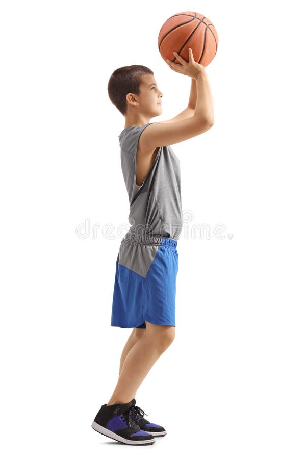 Kid throwing a basketball. Full length profile shot of a kid throwing a basketball isolated on white background stock photography