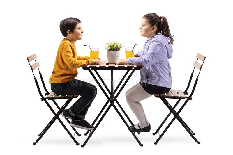 Little boy and girl sitting at a table with an orange juice stock photos