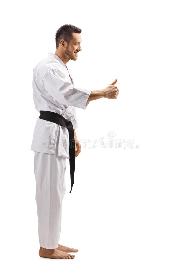 Man in karate kimono giving a thumb up. Full length profile shot of a man in karate kimono giving a thumb up isolated on white background stock photography