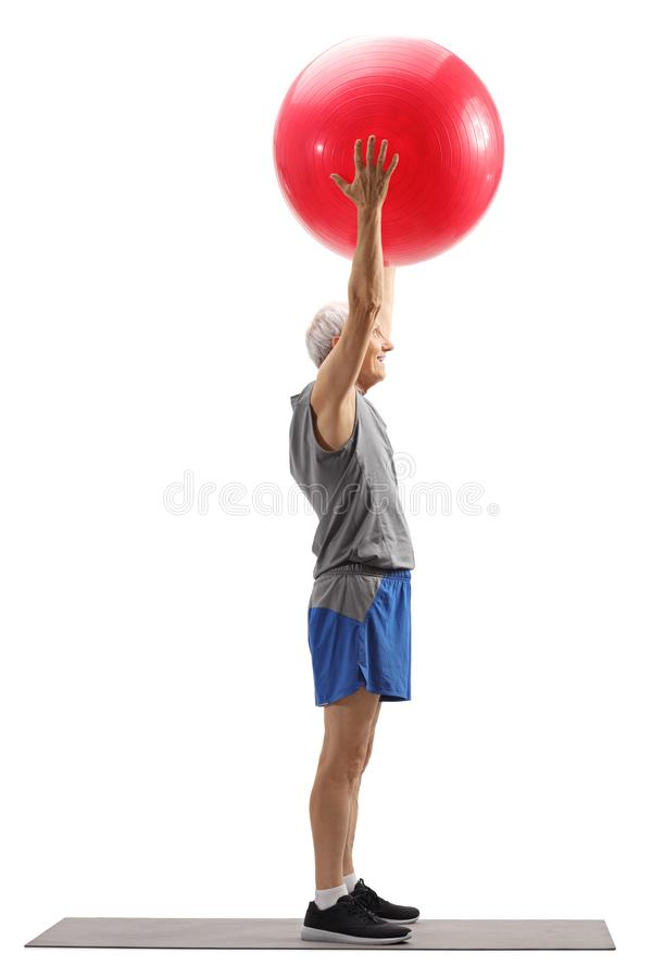 Senior man exercising pilates with a ball. Full length profile shot of a senior man exercising pilates with a ball isolated on white background stock image