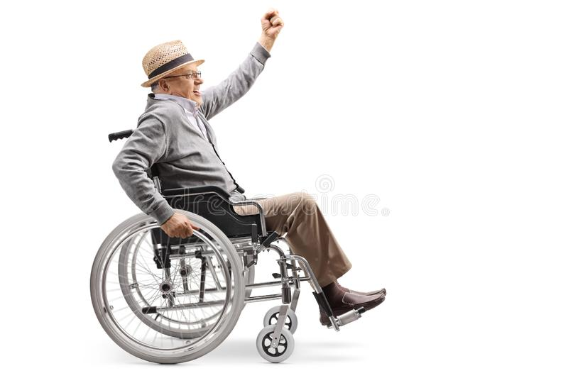 Senior man in a wheelchair pushing himself manually and raising a hand up. Full length profile shot of a senior man in a wheelchair pushing himself manually and stock photography
