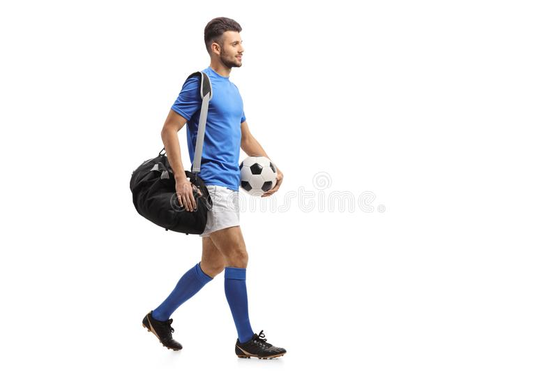 Soccer player with a bag and a football walking royalty free stock photo