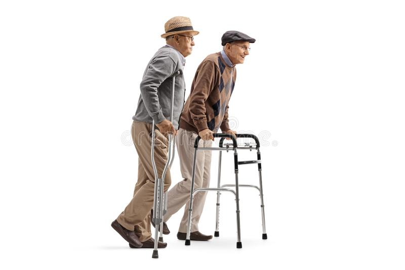 Two elderly men walking with crutches and walker. Full length profile shot of two elderly men walking with crutches and walker isolated on white background stock photos