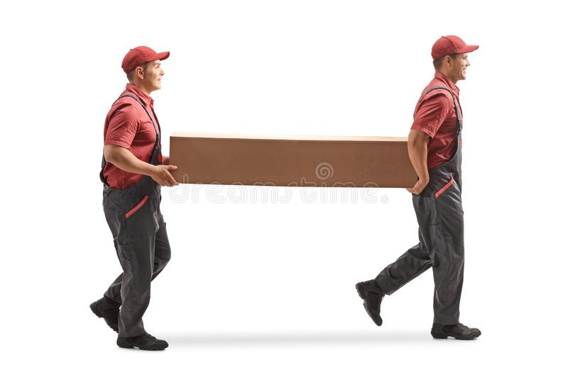 Two movers carrying a big cardboard box royalty free stock photo