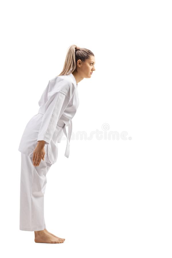 Full length profile shot of a woman in karate kimono bowing. Isolated on white background stock photo