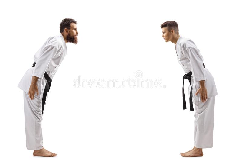 Young boy bowing to karate instructor. Full length profile shot of a young boy bowing to karate instructor isolated on white background stock photos