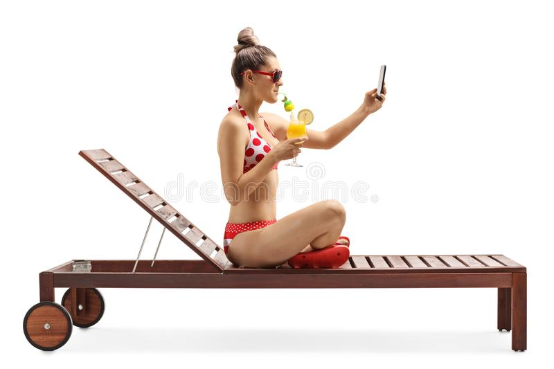 Young female in bikini sitting on a sunbed with a cocktail and taking a selfie photo royalty free stock image