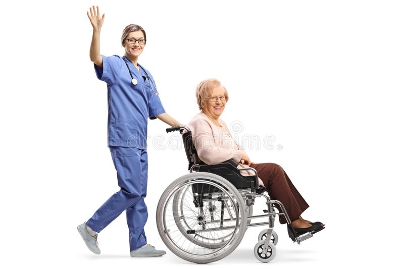 Young female nurse waving and pushing a senior woman in a wheelchair waving stock image