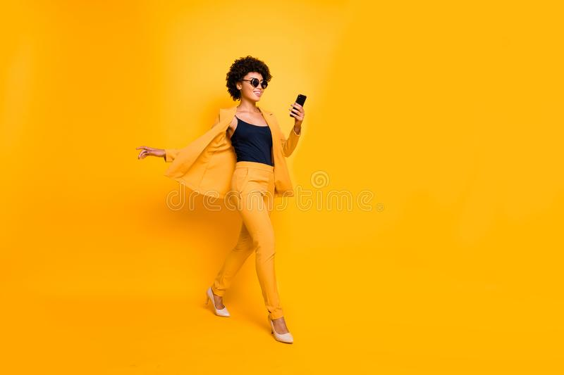 Full length profile side photo of positive afro american have spectacles weekend go use smartphone type sms on social royalty free stock photography