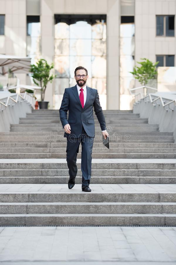 Full length of prosperous businessman walking down the stairs outside the office building. Middle aged successful businessman keeping a tablet in hand while stock photo