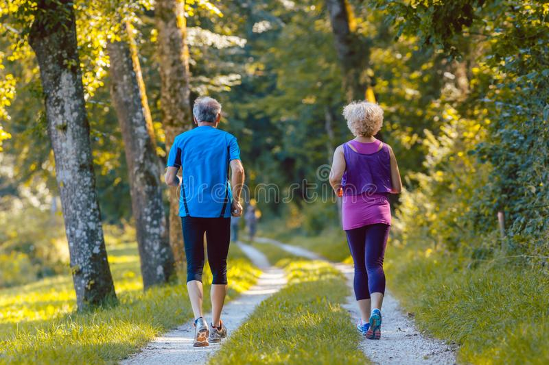 Full length rear view of a senior couple jogging together outdoors. Full length rear view of a senior couple wearing cool running outfits while jogging together stock images