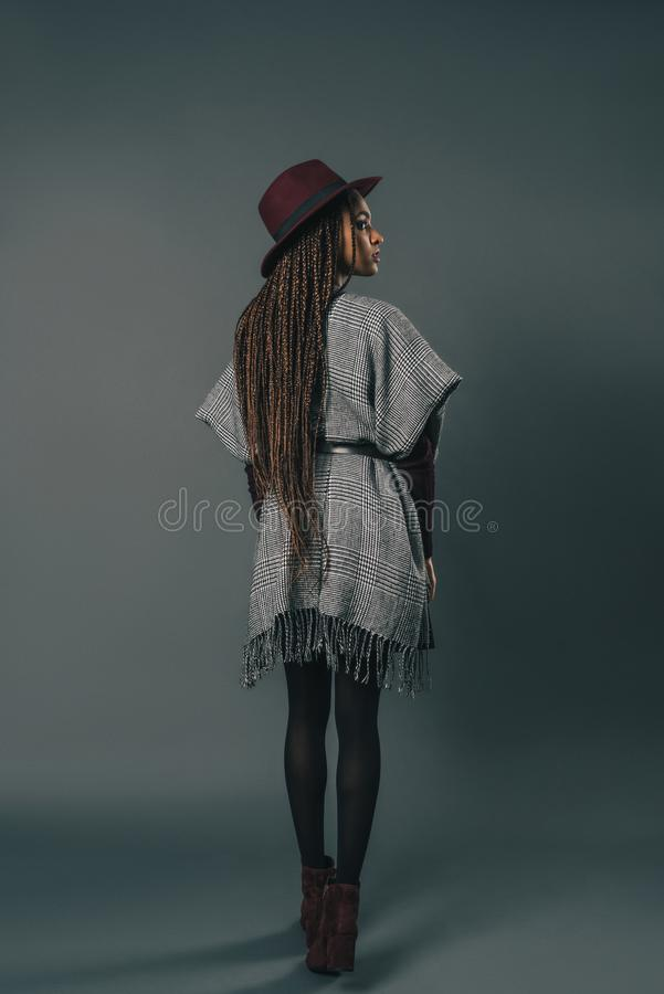 full length rear view of stylish young african american woman in hat standing stock photo