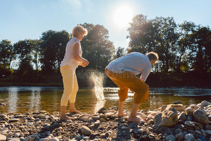 Two senior people enjoying retirement and simplicity. Full length rear view of two barefoot senior people enjoying retirement and simplicity while throwing stock photos