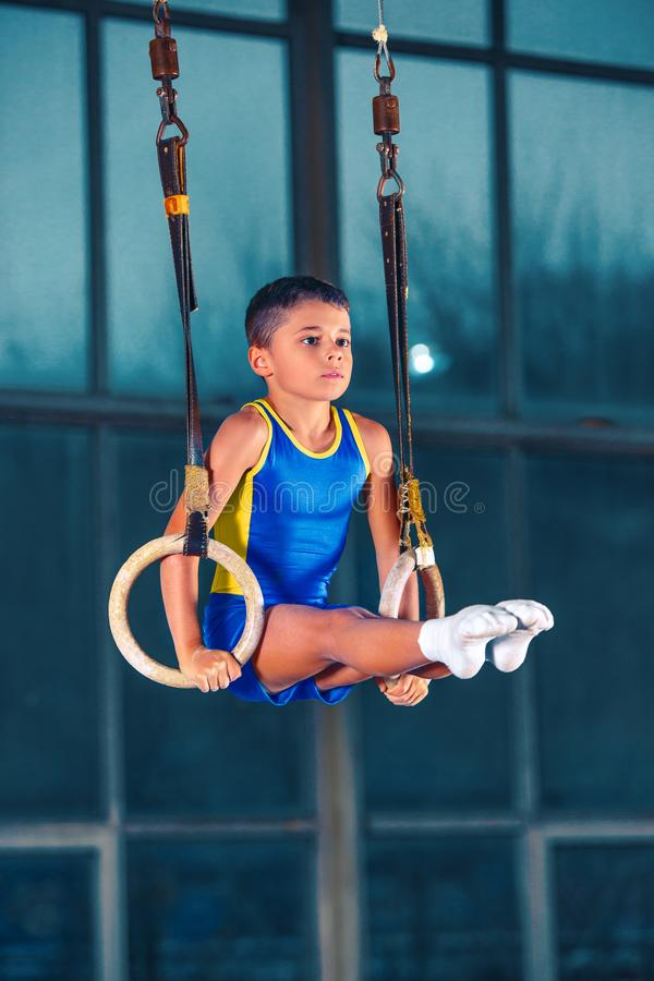 Full length rearview shot of a male athlete performing pull-ups on gymnastic rings. Full length shot of male athlete performing pull-ups on gymnastic rings royalty free stock image