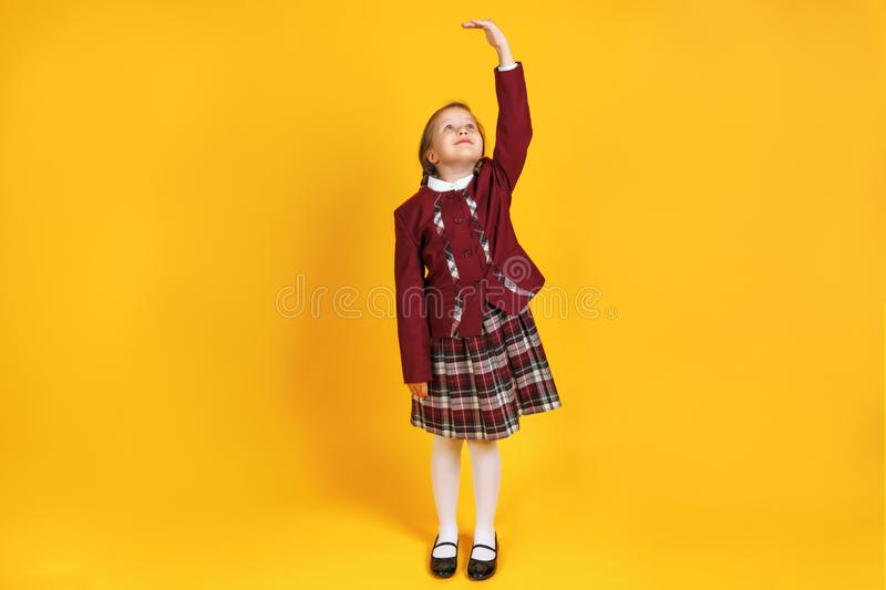 A full-length schoolgirl child in uniform is measuring her height. Little girl on a yellow background stock image