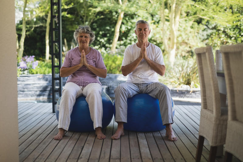Full length of senior couple meditating together while sitting at porch stock photos