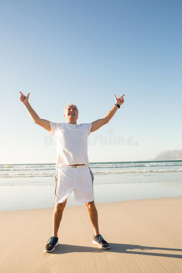 Full length of senior man with arms raised standing on sand against clear sky. At beach stock photo