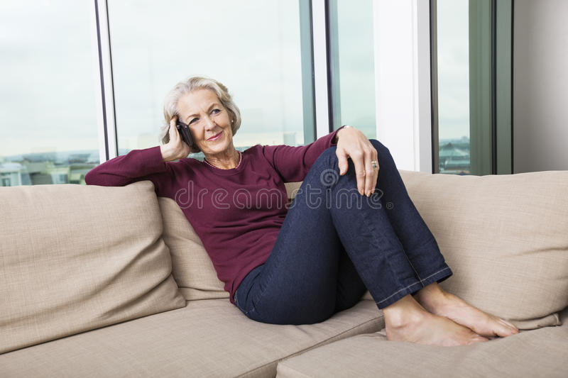 Full-length of senior woman answering smart phone on sofa at home stock photos