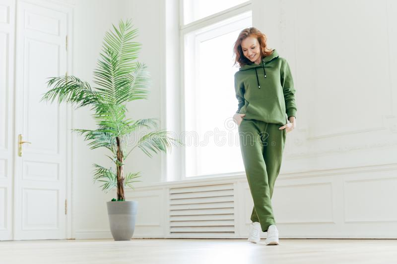 Full length shot of active pleased young woman with slim body, keeps hands in pockets of tracksuit, focused down, ready for doing royalty free stock photo