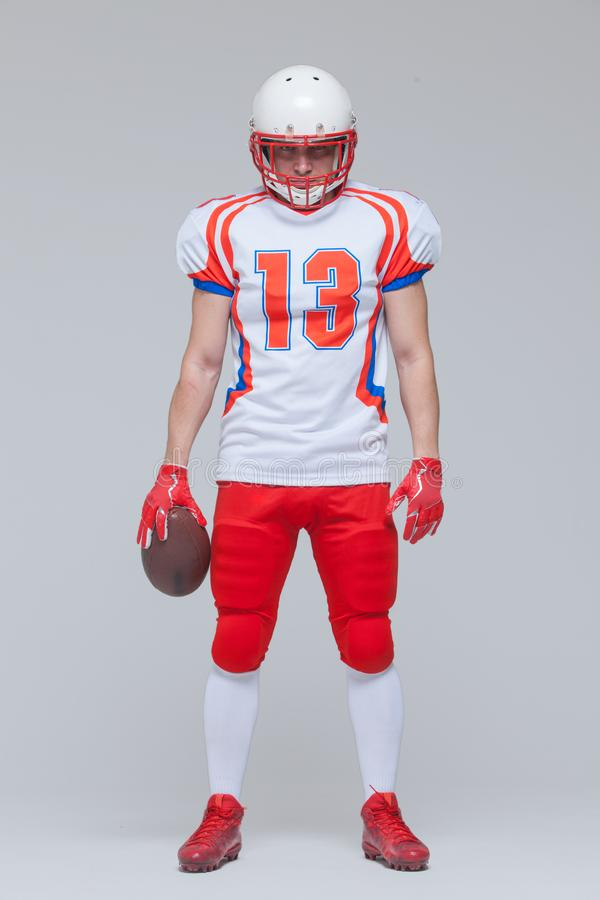 Full length shot of american football sportsman player wearing helmet holding rugby ball isolated on grey background royalty free stock photography