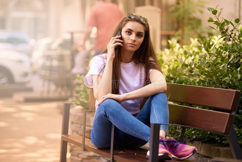 Beautiful young woman relaxing on the bench and making a call in the city stock images