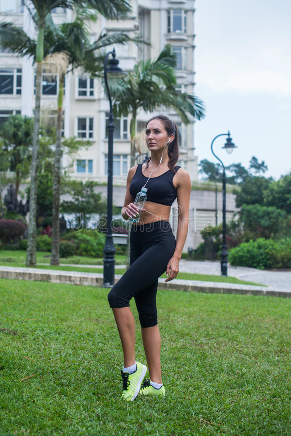 Full length shot of beautiful fitness female model in black sportswear standing on grass in city park and listening to stock photos