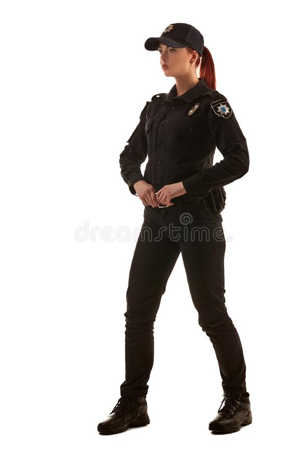 Full length shot of a redheaded female police officer posing for the camera isolated on white background. royalty free stock photo