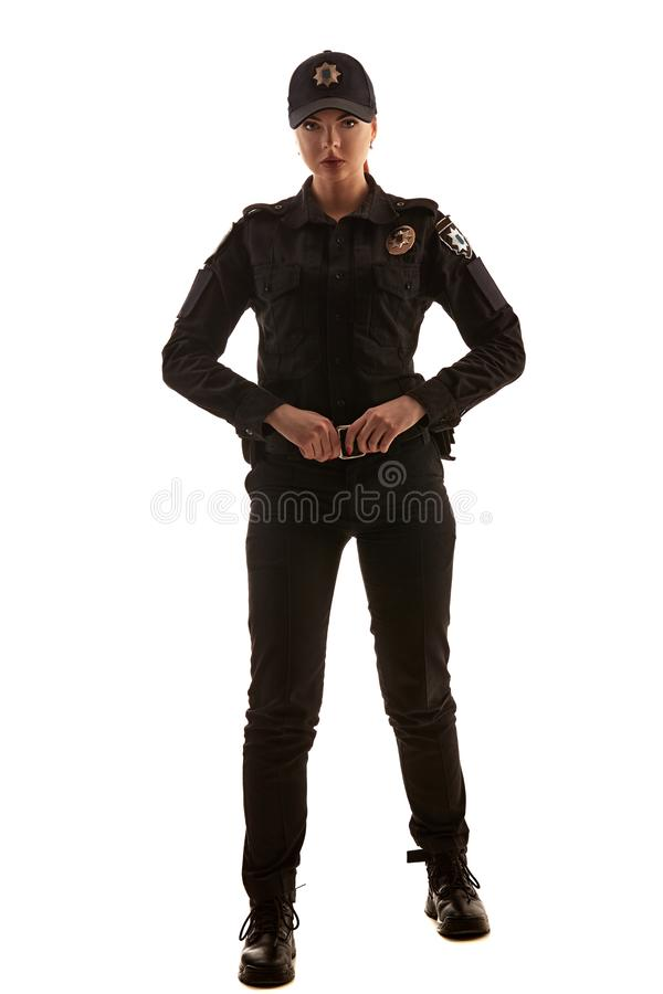 Full length shot of a redheaded female police officer posing for the camera isolated on white background. royalty free stock image