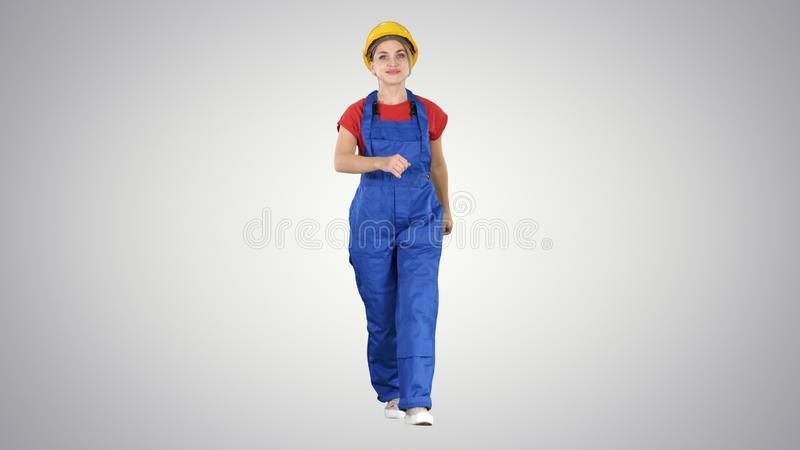 Confident experienced forewoman walking with will to work on gradient background. stock images