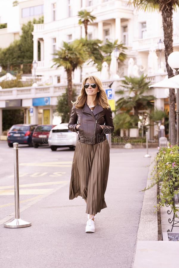 Attractive woman wearing fashionable clothes while walking on the street stock photos