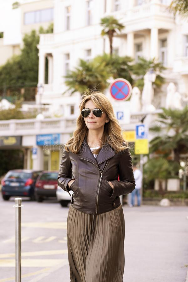 Attractive woman wearing fashionable clothes while walking on the street royalty free stock photo