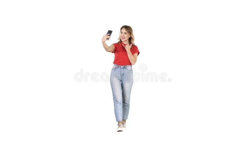 Cute girl with blond curly hair walking and making selfie on white background. royalty free stock photo