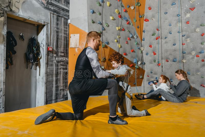 Full-length shot of dad securing his little son in a harness for climbing wall with grips. At gym royalty free stock image