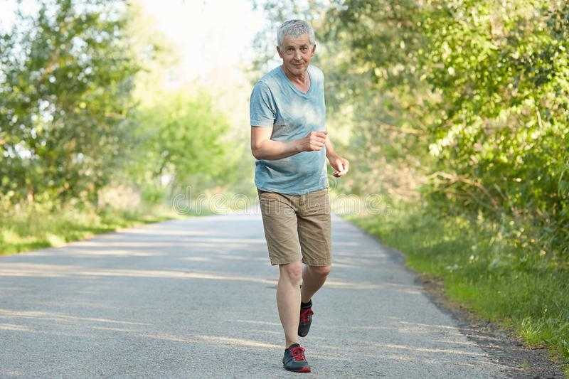 Full length shot of elderly male runner has outdoor training, runs on road in countryside, catches breath, has active healthy life stock photo