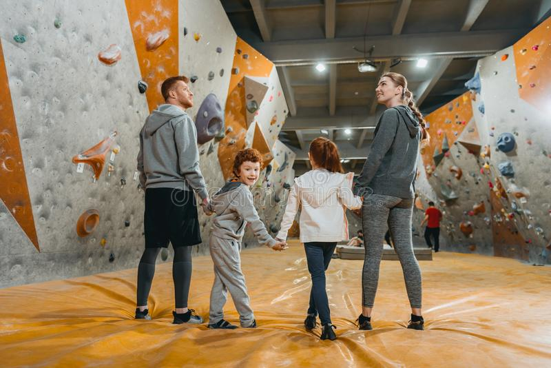 Full-length shot of family with kids holding hands and standing in a row. At gym stock image