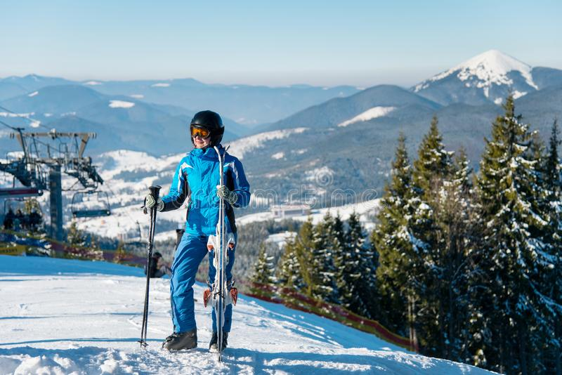 Full length shot of a female skier in winter sportswear posing on top of a mountain with her skis stock photos