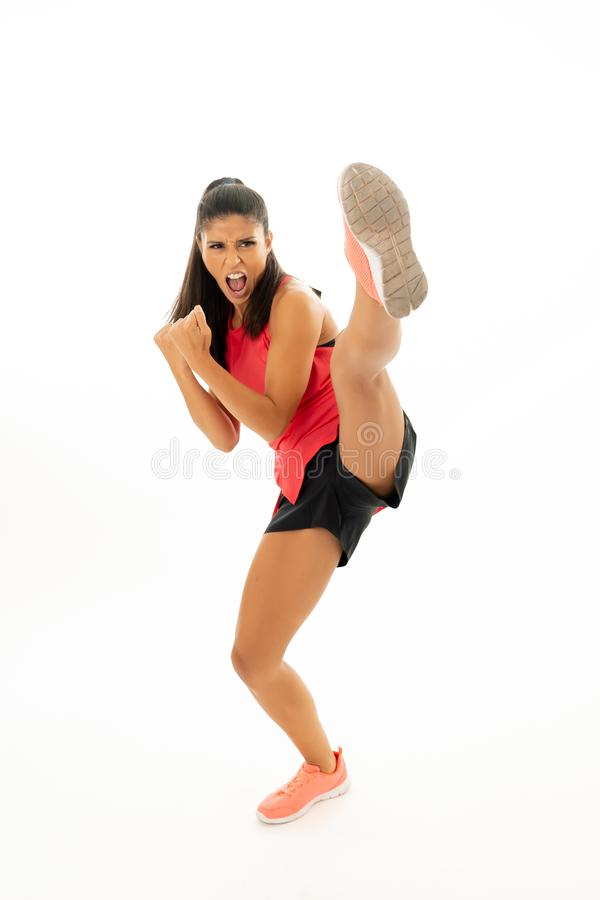 Full length shot of fit woman athlete performing a high kick martial Karate style. Young and furious latin woman in fight and kick boxing training workout royalty free stock photos